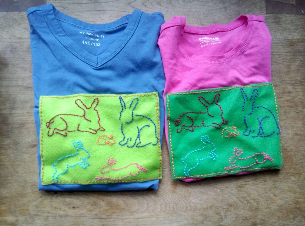 Twee shirts met daar op  geborduurde haasjes 2 grote en 3 klein waarvan een heel klein